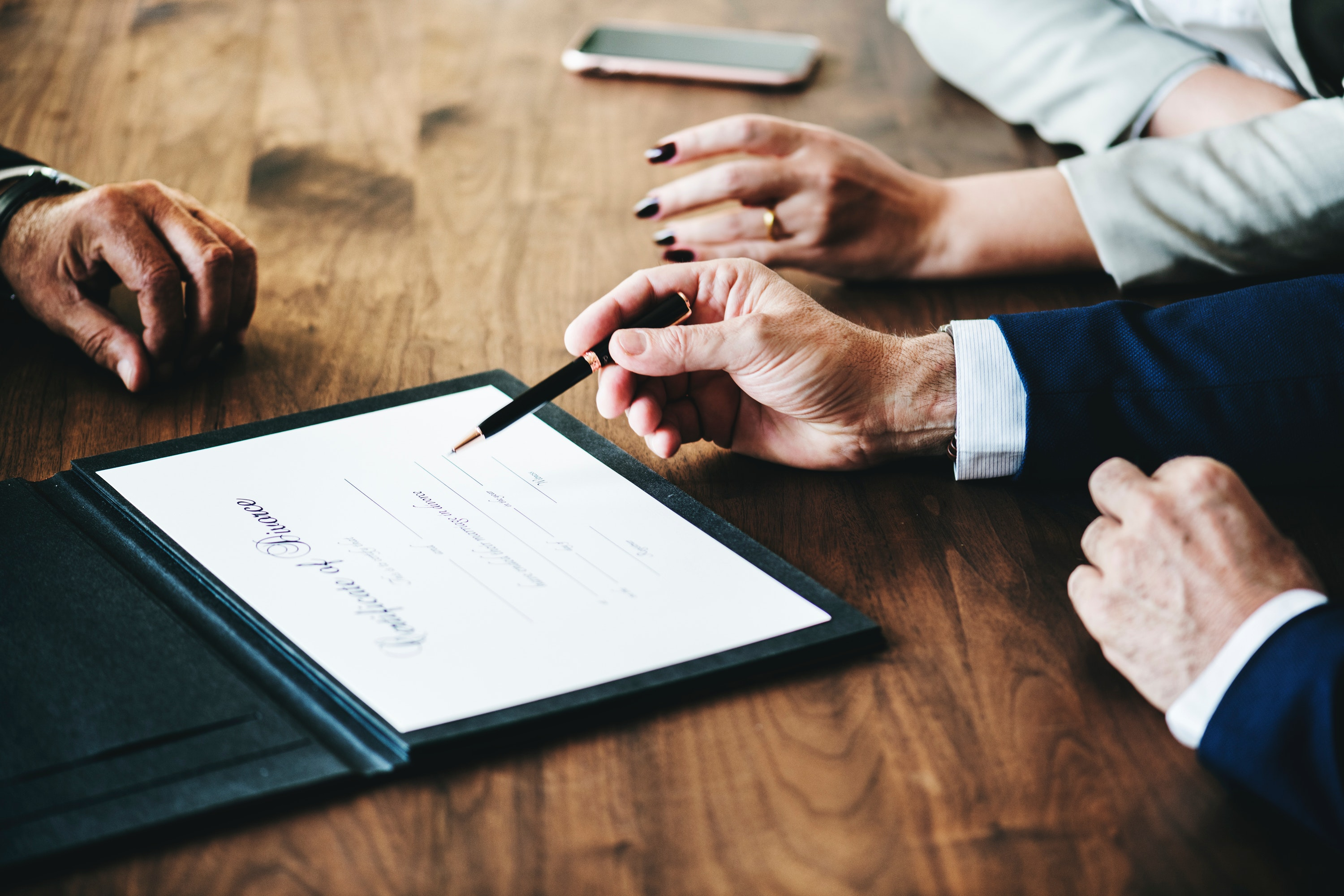 Couple signing divorce papers with lawyer