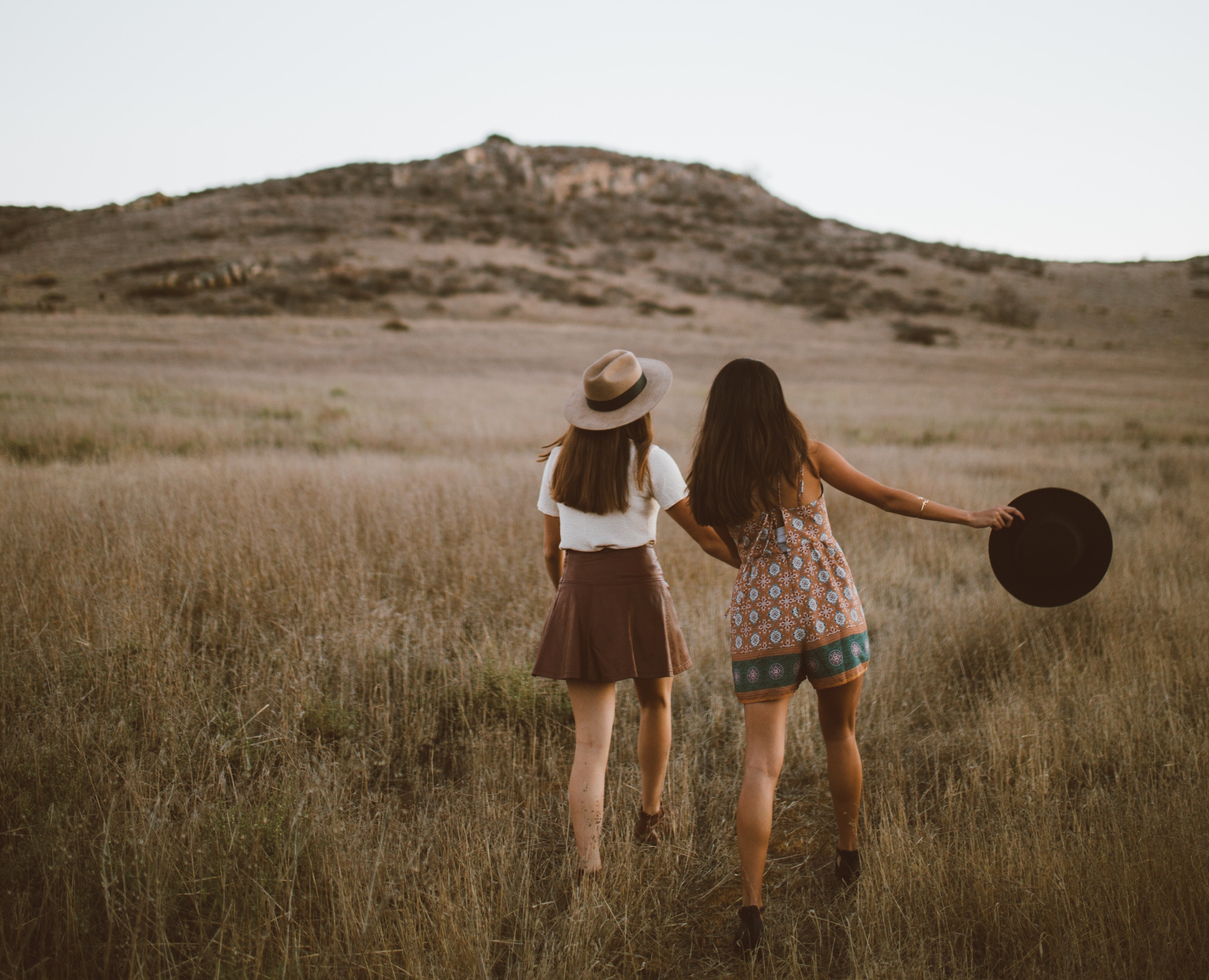 Two friends holding hands together in a field
