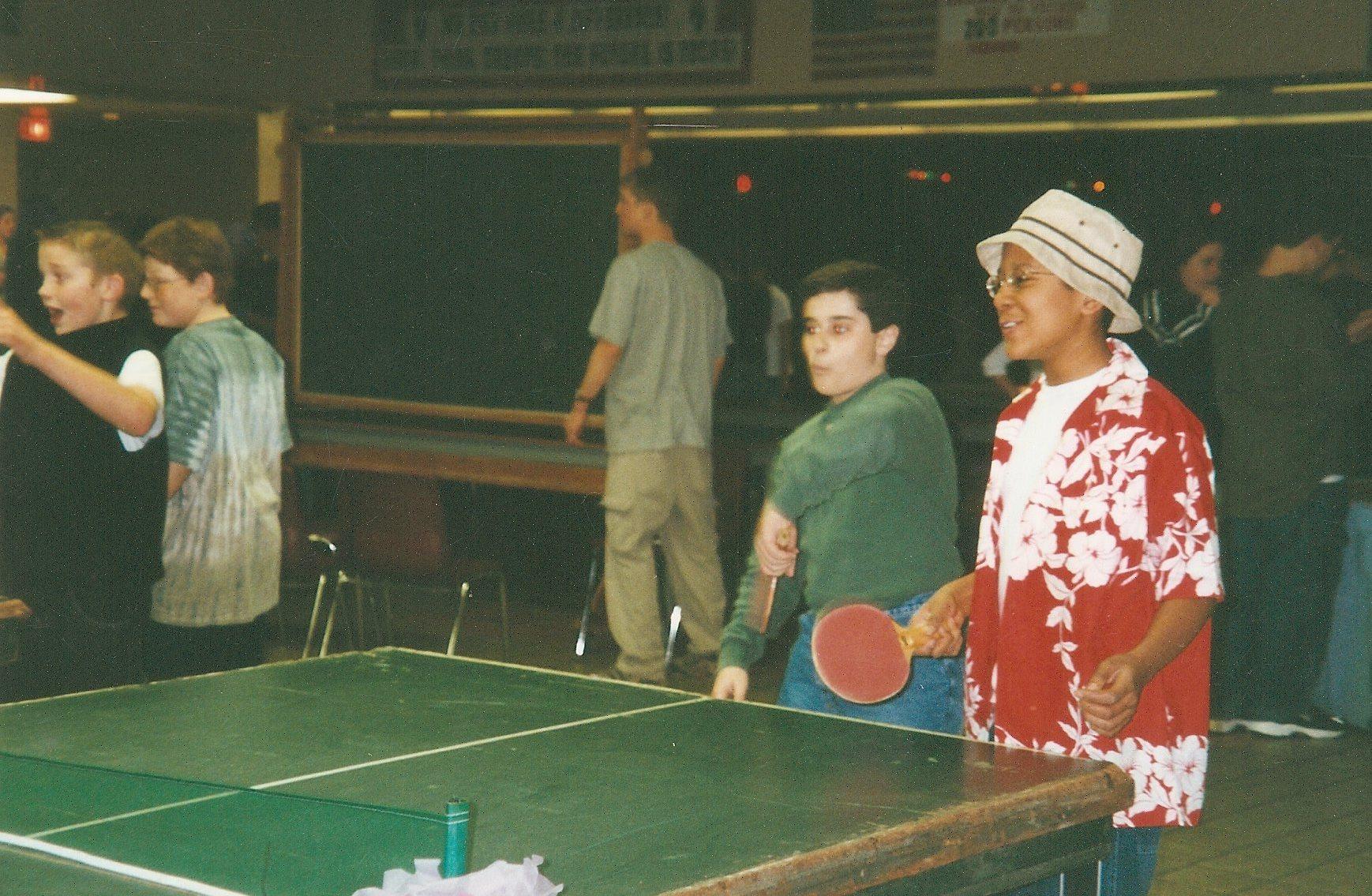 Two kids playing ping pong.