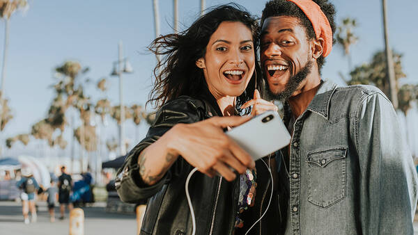 Man and woman smiling and taking selfie together