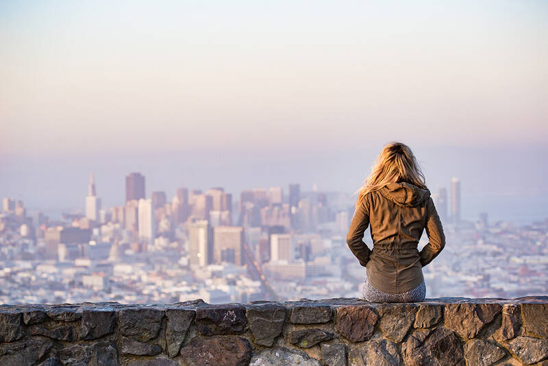 Woman sitting alone with view of city landscape