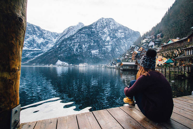 Woman sitting alone looking out at water and mountains